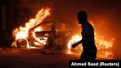 今年巴格達平民死亡人數比去年增加一倍多。巴格達一名男子看著爆炸後燃燒的汽車, 2013年10月7日。 (資料圖片)