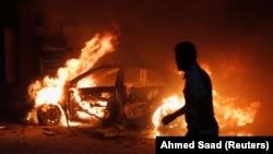 今年巴格达平民死亡人数比去年增加一倍多。巴格达一名男子看着爆炸后燃烧的汽车, 2013年10月7日。(资料图片)