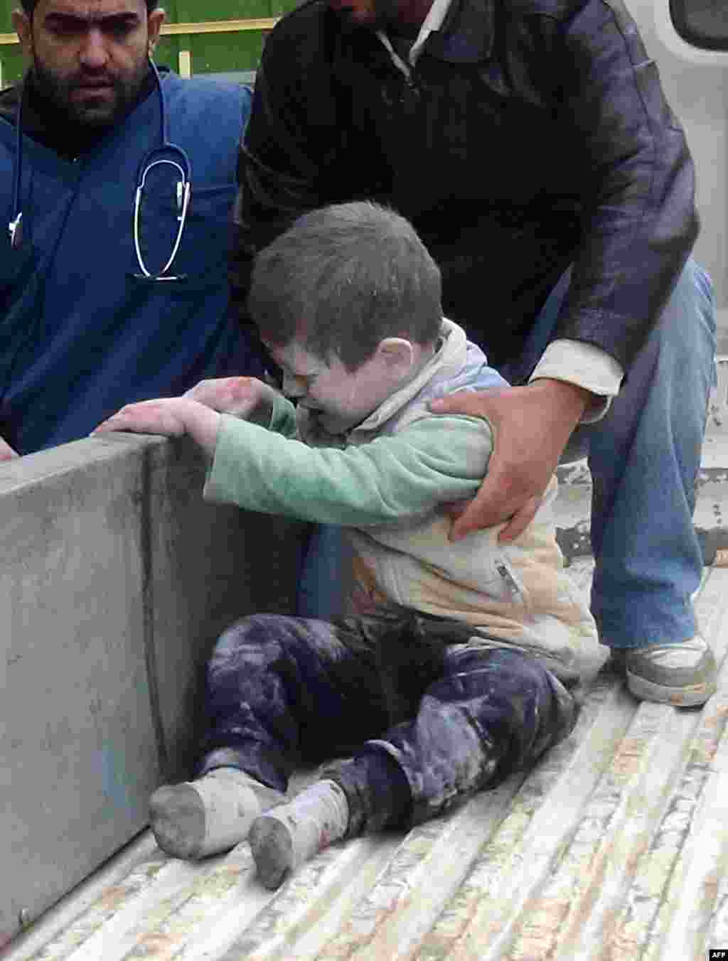 Syrians help an injured child following an alleged airstrike by government forces near a school in the northern city of Aleppo.