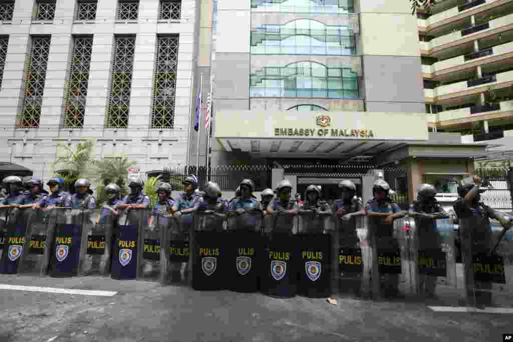 2013年3月5日,在示威者抗议马来西亚进攻婆罗洲岛的菲律宾武装组织后,防暴警察守卫着马尼拉以东的马来西亚大使馆。
