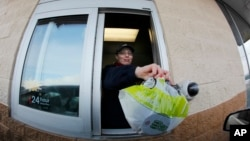 FILE – A fast food restaurant worker hands a patron a salad at a drive up window in Williamsville, New York.