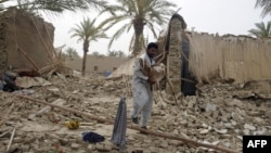 Pakistani earthquake survivor carries a goat among the rubble of collapsed mud houses in the Mashkail area of southwestern Baluchistan province on April 17, 2013.