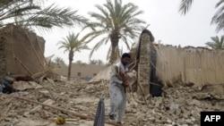 Seorang korban yang selamat dari gempa, menggendong seekor kambing yang ditemukannya diantara reruntuhan rumah di wilayah Mashkail, propinsi Baluchistan (17/4).