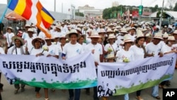 "Cambodians hold banners reading ""Voice of the poor in the city"" left, and ""Stop Forced Evictions"" right, as they march to the National Assembly during a rally to mark World Habitat Day, in Phnom Penh, Cambodia, file photo."
