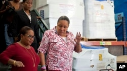 Haiti's Health Minister Florence Duperval Guillaume, left, leads a tour for first lady Sophia Martelly through a warehouse housing a donation of kits to treat chikungunya, in the Cite Soleil slum, in Port-au-Prince, Sept. 10, 2014.