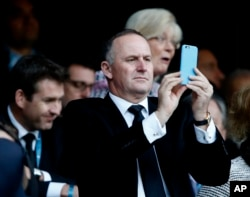 FILE - New Zealand Prime Minister John Key takes photo of the Rugby World Cup final between New Zealand and Australia at Twickenham Stadium, London, Oct. 31, 2015. Comments made by Key caused an uproar in parliament Tuesday.