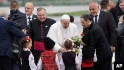 Папу Римського Франциска вітають діти у болгарських національних строях в аеропорту Софії 5 травня 2019 р.