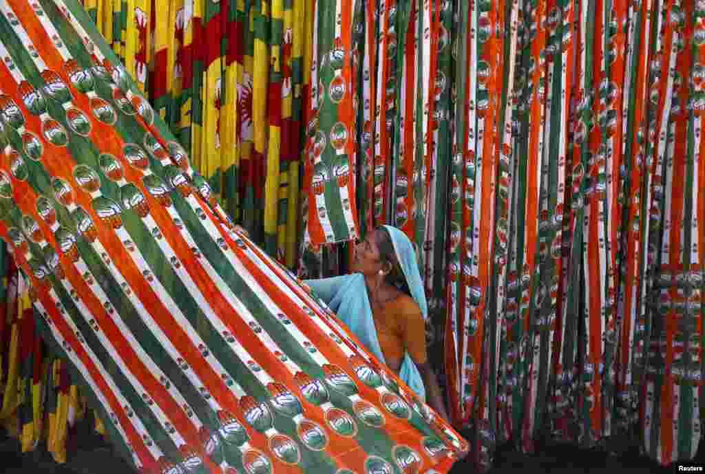 Một công nhân kéo một cuộn cờ của đảng Quốc đại Ấn Độ đương quyền, giữ cho khô tại một nhà máy sản xuất cờ, tại thành phố Ahmedabad miền tây Ấn Độ, trước cuộc tổng tuyển cử năm 2014