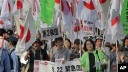 Ratusan pengunjuk rasa di Tokyo (22/9) menggusung bendera Jepang dalam aksi protes menentang klaim Tiongkok atas pulau sengketa Sengkaku (dalam bahasa Jepang). Pulau ini disebut Diayou dalam bahasa Tiongkok.
