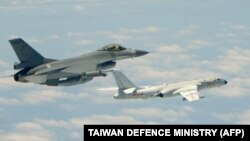 This handout photograph taken and released on May 11, 2018 by Taiwan's Defense Ministry shows a Republic of China (Taiwan) Air Force F-16 fighter aircraft (L) flying alongside a Chinese People's Liberation Army Air Force (PLAAF) H-6K bomber that entered its airspace.