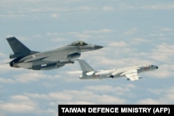 FILE - This handout photograph taken and released on May 11, 2018 by Taiwan's Defence Ministry shows a Republic of China (Taiwan) Air Force F-16 fighter aircraft (L) flying alongside a Chinese People's Liberation Army Air Force (PLAAF) H-6K bomber.