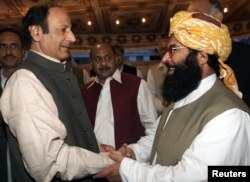 FILE - JUI-F Secretary General Abdul Ghafoor Haidari, right, greets Chaudhry Shujaat Hussein, parliamentary leader of the pro-military Pakistan Muslim League Quaid-e-Azam, at a reception hosted by PML-QA in Islamabad, Nov. 7, 2002.
