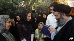 Iranian cleric Hossein Kazemeini Boroujerdi, right, consults with the Quran, as a woman asks for his guidance. (file)