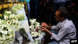 A Bangladeshi social activist lights a candle on floral arrangement that he placed on a road block leading to the Holey Artisan Bakery, the scene of a fatal attack and siege, in Dhaka on July 3, 2016.