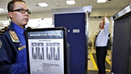 Transportation Security Administration screener Marlon Tejada, left, watches as Randy Parsons, TSA acting Federal Security Director, right, goes through a full body X-ray scanner for a security screening (File Photo)