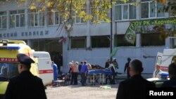 Polisi mengamankan lokasi terjadinya insiden, sementara petugas medis mengangkut para korban dalam serangan teror di kota Kerch, Krimea, Rabu (17/10).