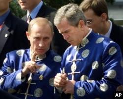 2001年10月21日 ,俄罗斯总统弗拉基米尔·普京和美国总统乔治·布什穿着中国传统丝绸外衣,在亚太经济合作组织(APEC)上海峰会上参加全家福合影时交谈。