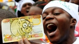 A protester displays a modified Kenyan 1,000 Shilling note ($12) imprinted with an image of a pig to depict what he says is greed in lawmakers demanding for a pay rise, during a demonstration in Nairobi, June 11, 2013.