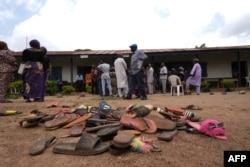 Barang-barang milik siswa Bethel Baptist High School berserakan di halaman sekolah saat orang tua siswa yang diculik berharap epulangan mereka, di Wilayah Pemerintah Daerah Chikun di negara bagian Kaduna, barat laut Nigeria, 14 Juli 2021. (Foto: AFP)