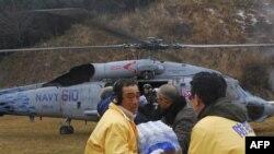 Японские добровольцы выгружают питьевую воду, доставленную вертолетом ВМФ США. Япония. 16 марта 2011 года