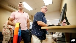 Chris Walters, izquierda, y Bill Reyno, derecha, llenan una solicitud en línea en el Condado de Dallas, Texas, para una licencia de matrimonio, el viernes, 26 de junio de 2015.