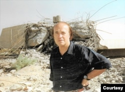Peter Arnett trước một khu dân cư đổ nát do bị oanh tạc vì quân đội cho là có thể là nơi ẩn náu của kẻ thù. Các tường trình từ Baghdad như vậy của ông đã bị quân đội và giới ủng hộ chiến tranh chỉ trích, theo lời ông. (Hình: Peter Arnett cung cấp)
