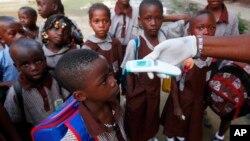 Una maestra usa un termómetro a distancia para tomar la temperatura de los estudiantes en una escuela primaria de Lagos, Nigeria.
