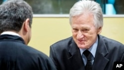 Gen. Momcilo Perisic, former chief of staff of the Yugoslav national army, right, talks to his lawyer prior to appeal judgment The Hague, Feb. 28, 2013.