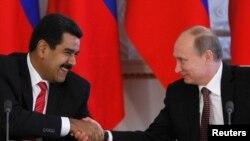 Presiden Rusia Vladimir Putin (kanan) berjabat tangan dengan Presiden Venezuela Nicolas Maduro dalam upacara penandatanganan kerjasama di Kremlin, Moskow (2/7). Presiden Maduro secara lisan mendukung Snowden yang kini menjadi buronan pemerintah AS, dalam upayanya mencari perlindungan politik.
