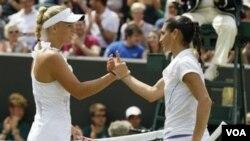 Petenis Denmark Caroline Wozniacki bersalaman setelah mengalahkan petenis Perancis Virginie Razzano di Wimbledon, Jumat (24/6).