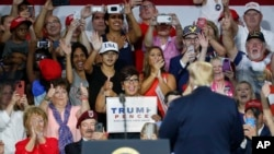 Supporters cheer for President Donald Trump, right, during a rally, Aug. 4, 2018, in Lewis Center, Ohio.