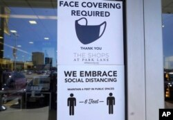 Signs tells customers about safety measures against COVID-19 that are required inside a retail store Tuesday, March 2, 2021, in Dallas.
