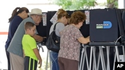 FILE - Florida voters fill out there ballots in the primary election, August 30, 2016, in Hialeah, Florida. A federal judge extended the deadline to register to vote in Florida in the wake of Hurricane Matthew.