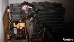 Một chiến binh phe nổi dậy xem các võ khí tịch thu được tai một căn cứ quân sự ở làng Hawa, nằm về hướng bắc thành phố Aleppo, 23/12/12