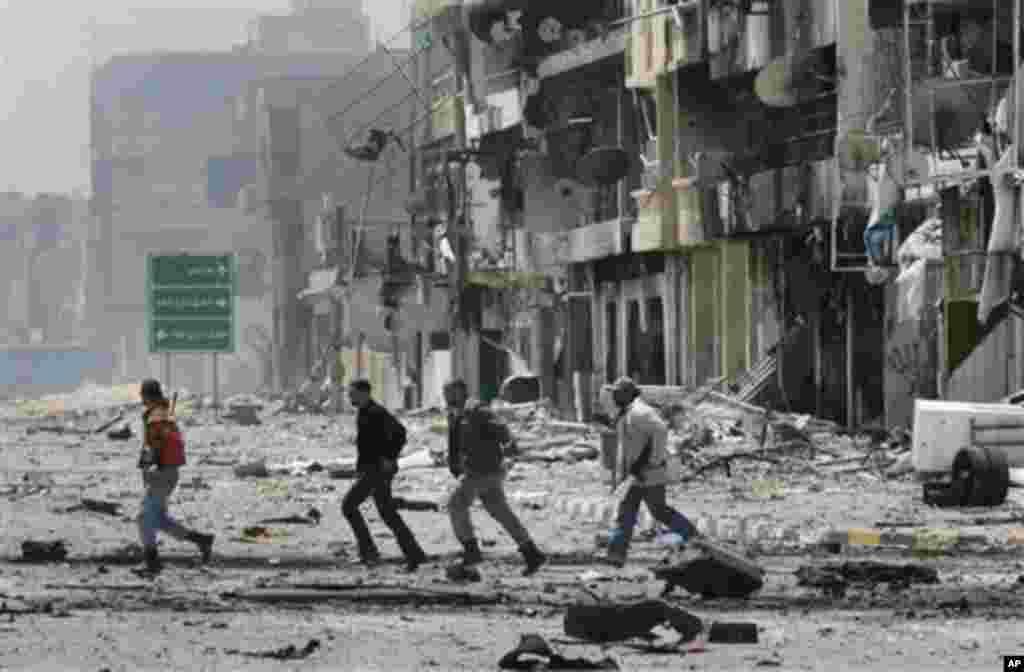 Libyan rebel fighters run across a street in Misrata, April 23, 2011. (AP image)