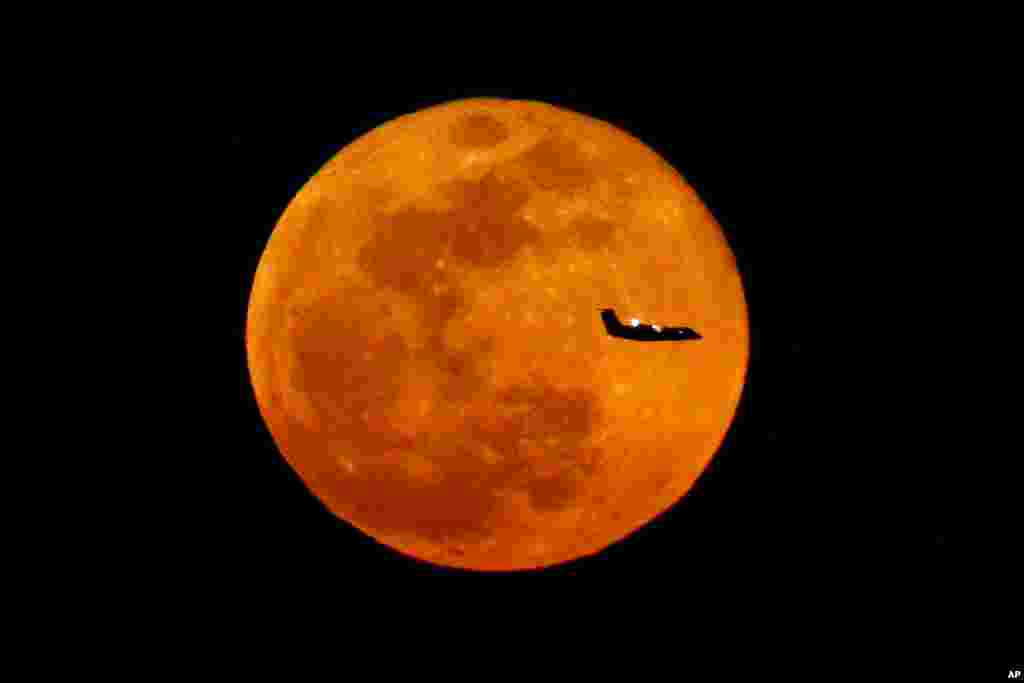 A plane descending into Newark Liberty International Airport crosses over the full moon rising as seen from the Eagle Rock Reservation in West Orange, New Jersey, March 23, 2016.