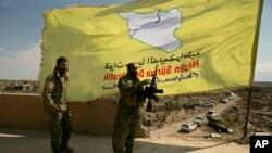 Các chiến binh của lực lượng SDF đứng trên sân thượng nhìn ra Baghouz, Syria, sau khi SDF tuyên bố giải phóng cứ điểm cuối cùng mà Nhà nước Hồi giáo nắm giữ ở Syria, ngày 23 tháng 3, 2019.