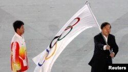 Nanjing Mayor Ji Jianye (R) waves the Olympic flag beside Chinese athlete Gao Tingjie during the closing ceremony of the Singapore 2010 Youth Olympic Games (YOG) at the Marina Bay Floating Platform in Singapore, Aug. 26, 2010.