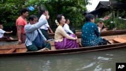 Myanmar opposition leader Aung San Suu Kyi, center, rides a boat on her way to a monastery where flood victims are sheltered, in Bago, northeast of Yangon, Myanmar, Aug. 3, 2015.