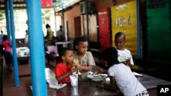 FILE - Expat children break for lunch at the American International School in Conakry, Guinea