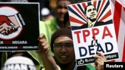 Protestors wave placards at a rally against the Trans Pacific Partnership (TPP) just days before parliament is due to open a debate on the free trade pact in Kuala Lumpur, Malaysia, January 23, 2016.