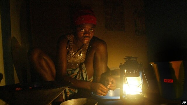 A displaced girl sits in a Monrovia hotel without electricity or water preparing lunch for her family on Tuesday, Sept 2, 2003.