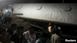 Police and members of the rescue operation stand at the site of a train derailment near Harda, Madhya Pradesh in this handout provided by ANI on August 5, 2015.