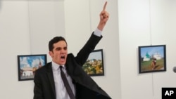 A gunman gestures after shooting the Russian Ambassador to Turkey, Andrei Karlov, at a photo gallery in Ankara, Turkey, Monday, Dec. 19, 2016.