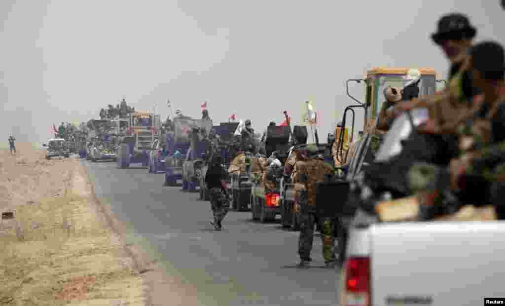 Shi'ite paramilitary forces ride military vehicles traveling from Lake Tharthar toward Ramadi to fight against Islamic state militants, west of Samarra, Iraq May 27, 2015.