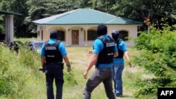 Honduran authorities at a seized property in Copan which belongs to the family of Digna Azucena Valle in Copan, who is imprisoned in the US on drug charges, August 18, 2014.