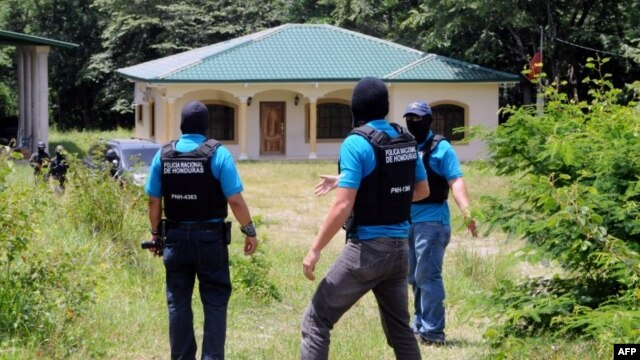 Image released by the Honduran government shows Honduran authorities at a seized property in Copan, which belongs to the family of Digna Azucena Valle, who is imprisoned in the US on drug charges, August 18, 2014.