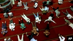 FILE - Muslim men nap as they wait for the time to break their fast after Friday prayer at the Istiqlal Mosque in Jakarta, Indonesia, Friday, June 9, 2017. Muslims across the world are observing the holy fasting month of Ramadan, where they refrain from eating, drinking and smoking from dawn to dusk. (AP Photo/Tatan Syuflana)