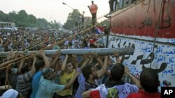 Protesters tear down a concrete wall built in front of the Israeli embassy in Cairo, Egypt, September 9, 2011