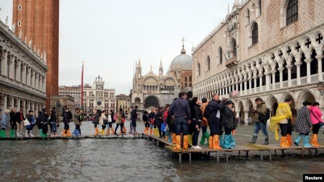 "Lapangan Santo Mark di Venesia, Italia tampak ""digenangi air"" pada saat air pasang di sana (29/10)."